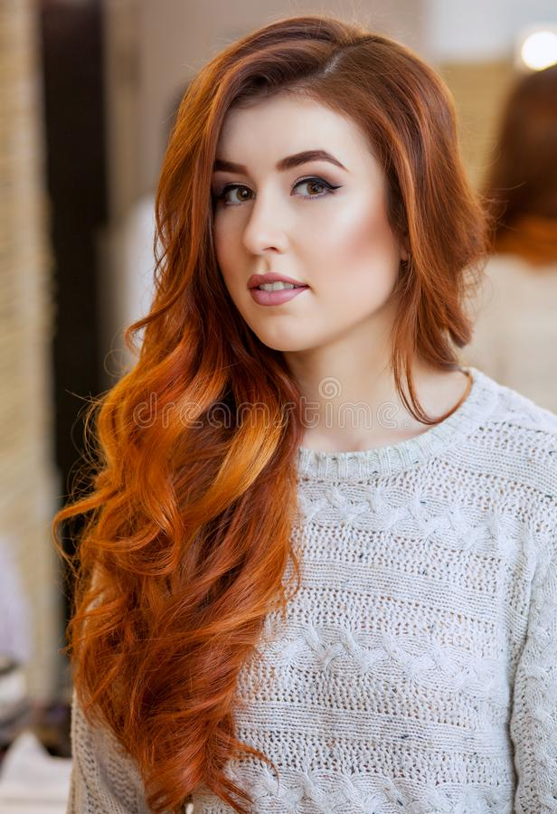 Stående av en härlig rödhårig flicka med långt hår i en skönhetsalong royaltyfria bilder