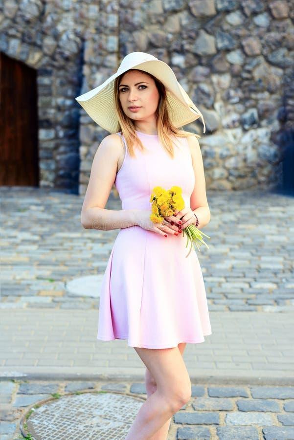 Stående av en härlig romantisk caucasian flicka i en hatt med blommor i hans hand i en rosa klänning arkivbilder