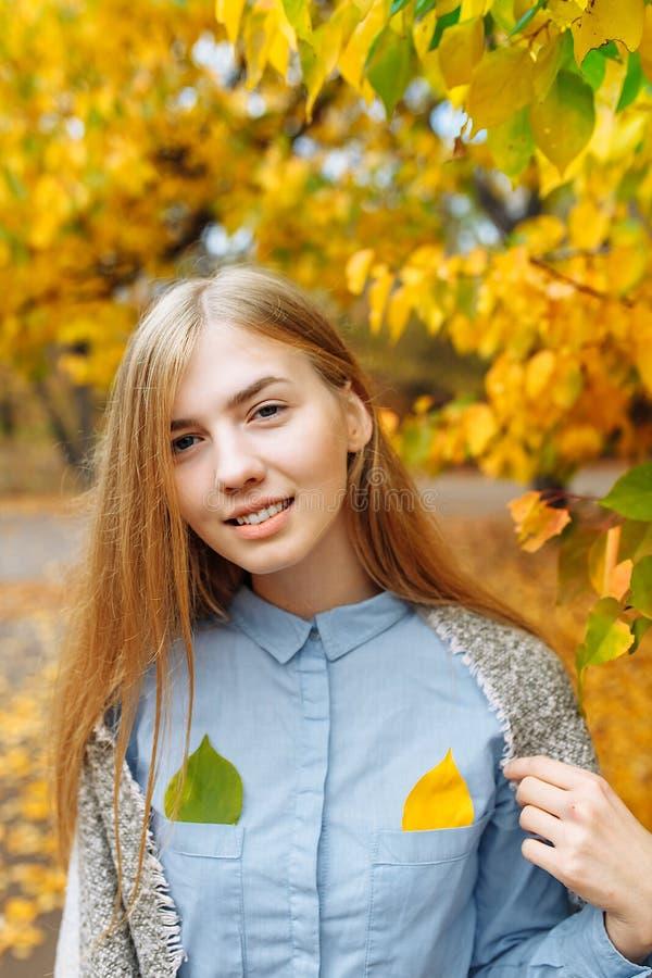 Stående av en härlig, söt gladlynt flicka som går i parkera i höstsäsong royaltyfria foton