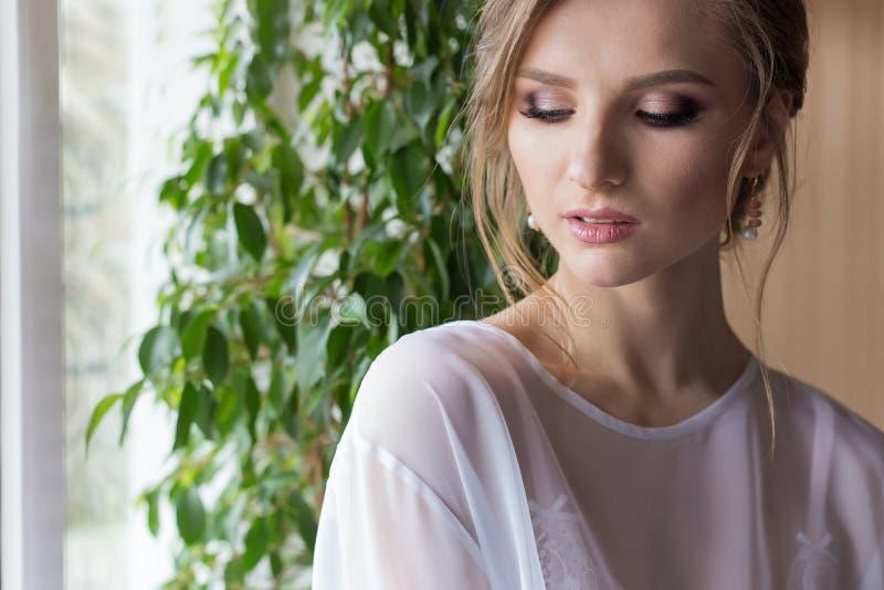 Stående av en härlig sexig gullig flickabrud i en vit klänning med den delikata makeup- och aftonfrisyren arkivfoto