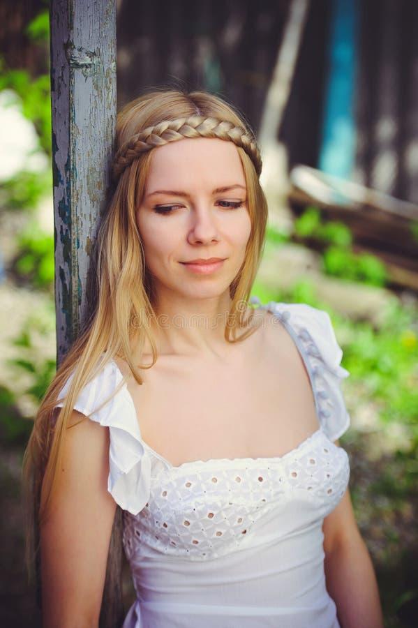 Stående av en härlig sexig kvinna, härliga kanter och en blygsam blick som bär en vit klänning arkivbilder