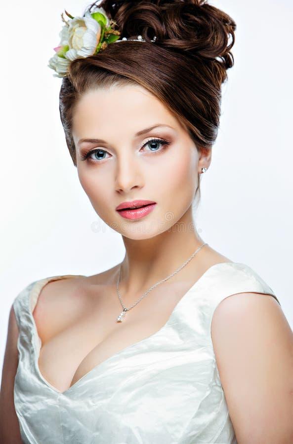 Stående av en härlig sinnlig flicka med en stor byst och blommor royaltyfria bilder