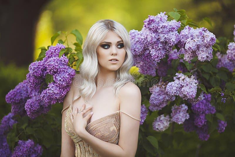 Stående av en härlig sinnlig ung blond kvinna i vår den blomstra dagträdgården kan spring soligt Ung flicka i en guld- klänning royaltyfria foton