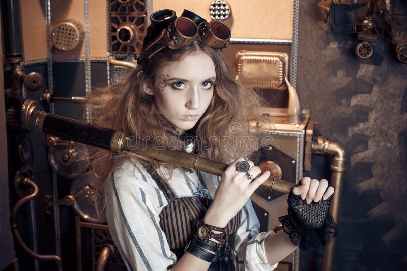 Stående av en härlig steampunkkvinna, med ett teleskop på ett G royaltyfria foton