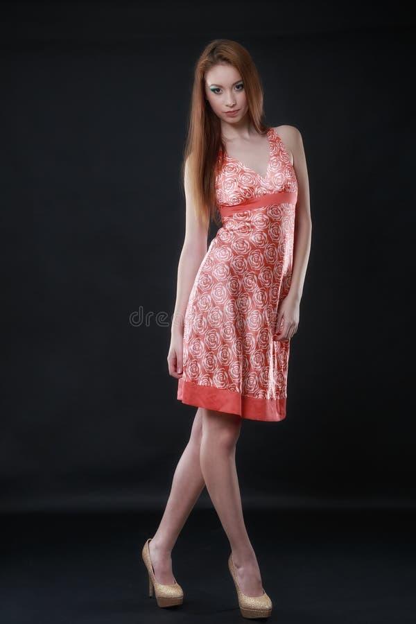 Stående av en härlig tillfällig kvinna i färgrik klänning arkivfoto