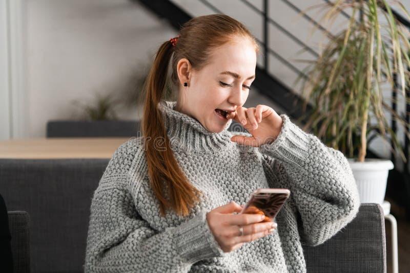 Stående av en härlig tonåring som kopplar av och använder en mobiltelefon för att ha en konversation med vänner som ler och arkivfoton