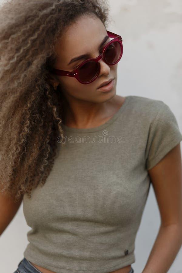 Stående av en härlig trendig ung lockig kvinna med rosa färger arkivfoto