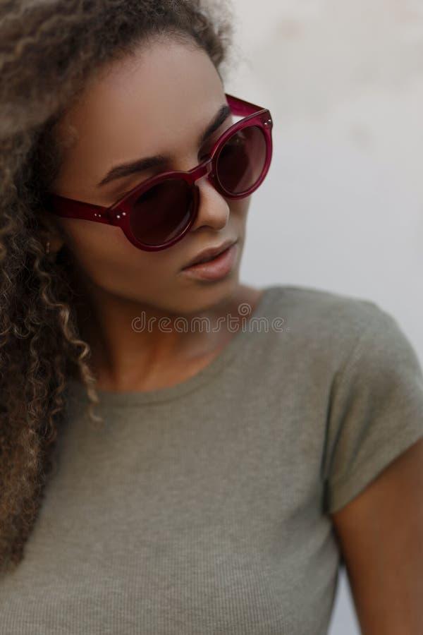 Stående av en härlig trendig ung lockig kvinna med rosa färger royaltyfria foton