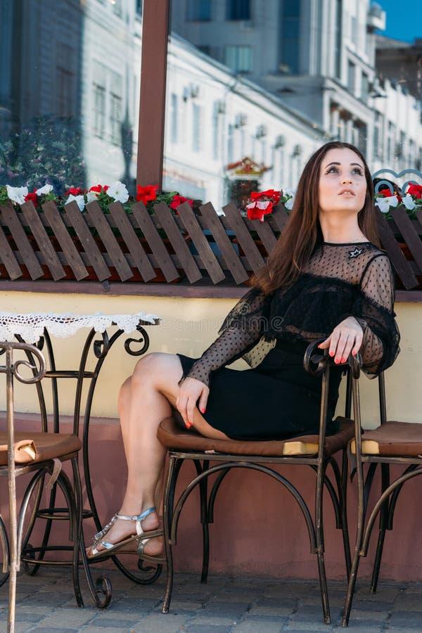 Stående av en härlig, ung attraktiv flicka som sitter på gatan i ett kafé väntande på frukost, sommar, datum dröm royaltyfria foton