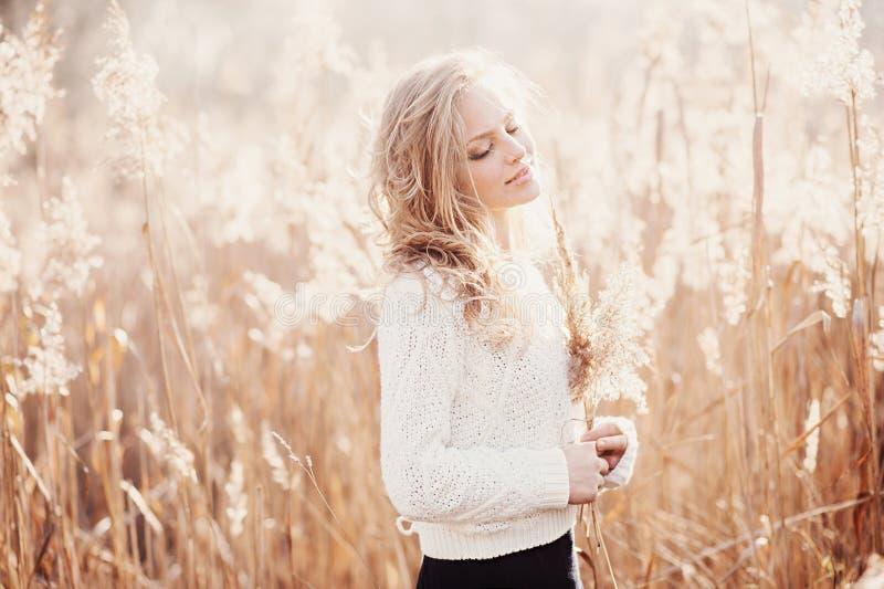 Stående av en härlig ung blond flicka i ett fält i den vita sweatern som ler med stängda ögon, begreppsskönhet och hälsa royaltyfria bilder