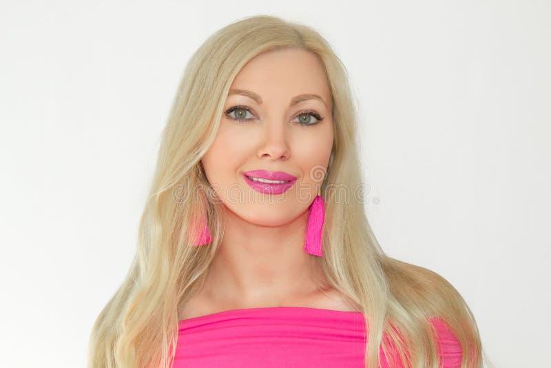 Stående av en härlig ung blond kvinna i rosa färger, med ett trevligt gulligt leende på en vit bakgrund royaltyfria bilder
