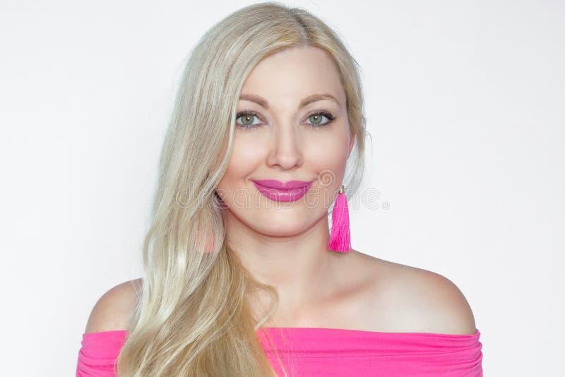 Stående av en härlig ung blond kvinna i rosa färger, med ett trevligt gulligt leende på en vit bakgrund arkivbilder