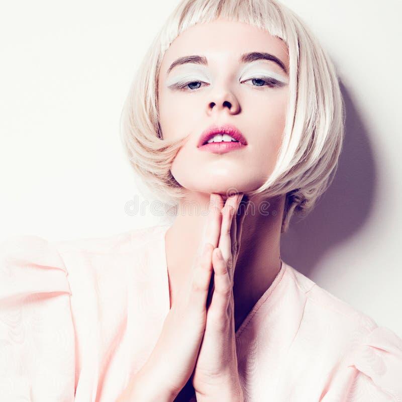 Stående av en härlig ung blond kvinna med kort hår i studion på en vit bakgrund, begrepp av skönhet, slut upp royaltyfri bild