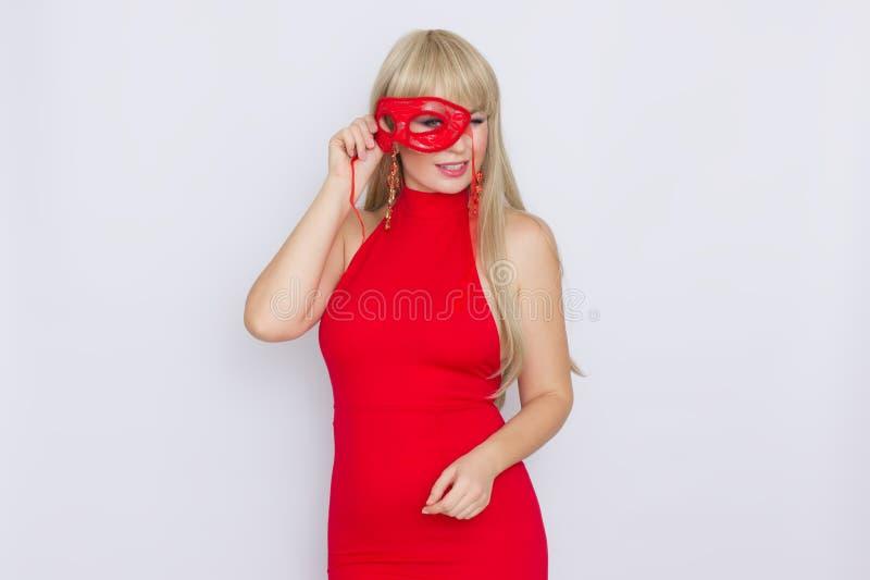 Stående av en härlig ung blond kvinna med långt hår i en röd aftonklänning Flickan sätter på en röd karnevalmaskering över vit royaltyfria bilder