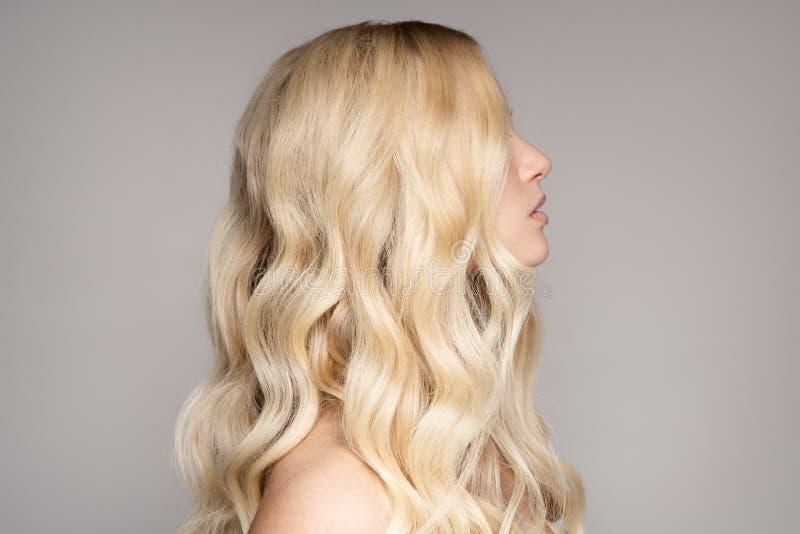 Stående av en härlig ung blond kvinna med långt krabbt hår royaltyfri foto