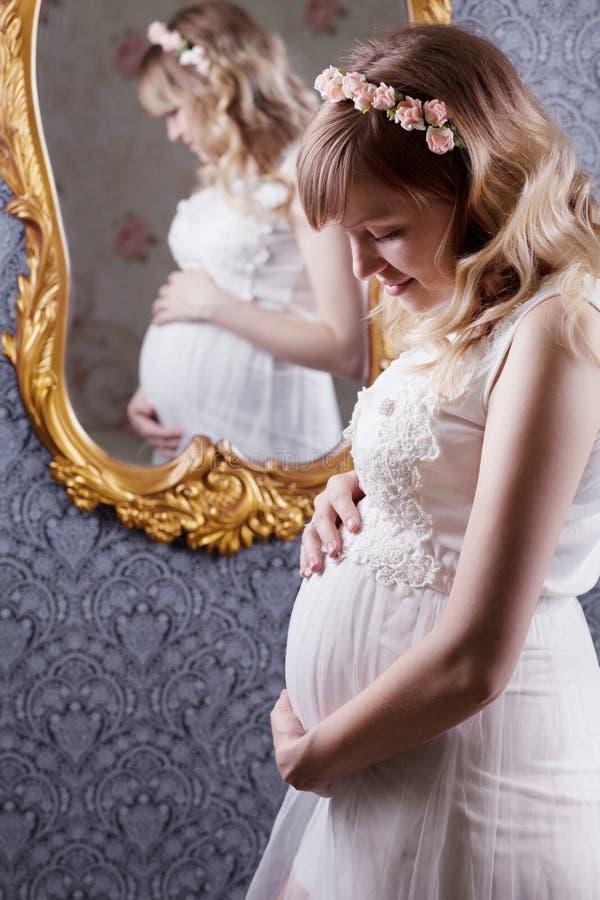 Stående av en härlig, ung blond långhårig gravid moder i en vit tappningpeignoir, med en blom- vink på hennes huvud arkivbilder