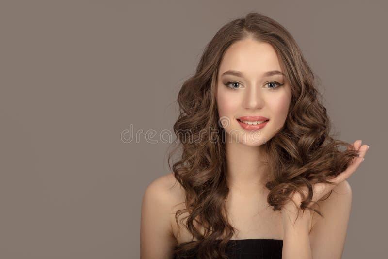 Stående av en härlig ung brunett med långt krabbt hår royaltyfri fotografi
