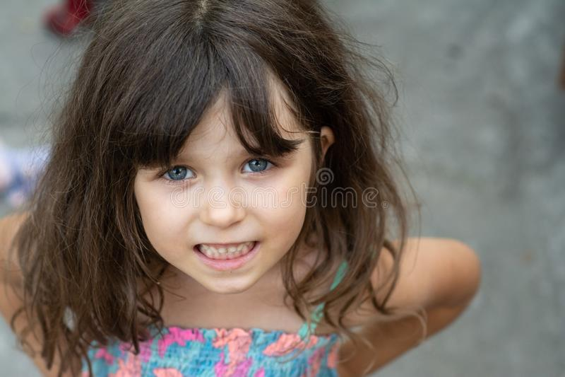 Stående av en härlig ung brunettliten flicka, lockigt hår, blåa ögon som bär en sommarklänning royaltyfri foto