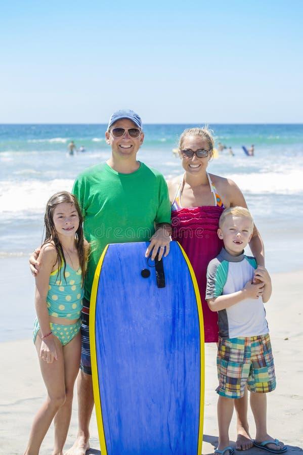 Stående av en härlig ung familj på stranden arkivfoto