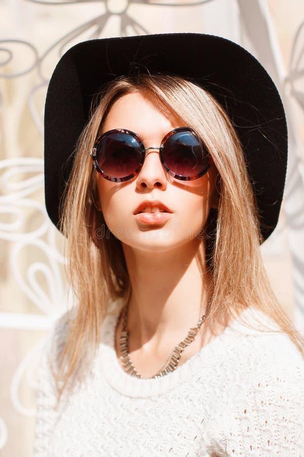 Stående av en härlig ung flicka i en sjöng svart hatt och runda arkivfoton