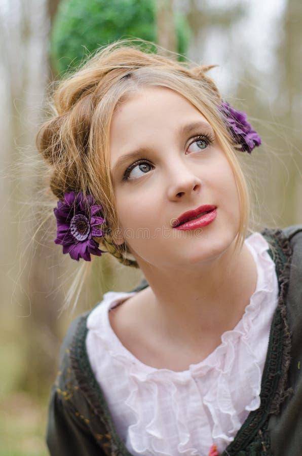 Stående av en härlig ung flicka med dekorativa blommor i H arkivfoton