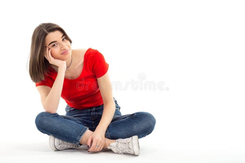 Stående av en härlig ung flicka som bär rött t-skjorta sammanträde på golvet, ben som korsas mot vit bakgrund, studiofors royaltyfria foton