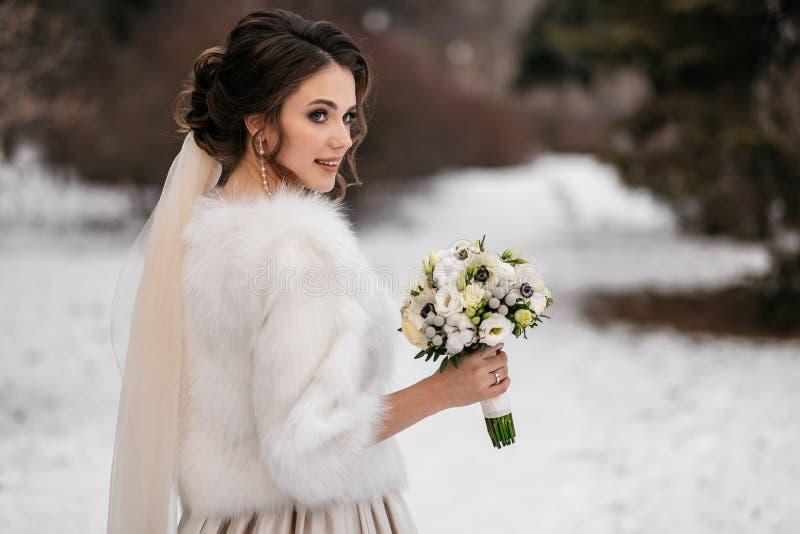 Stående av en härlig ung kvinna, brud, i en vinterskog royaltyfri bild