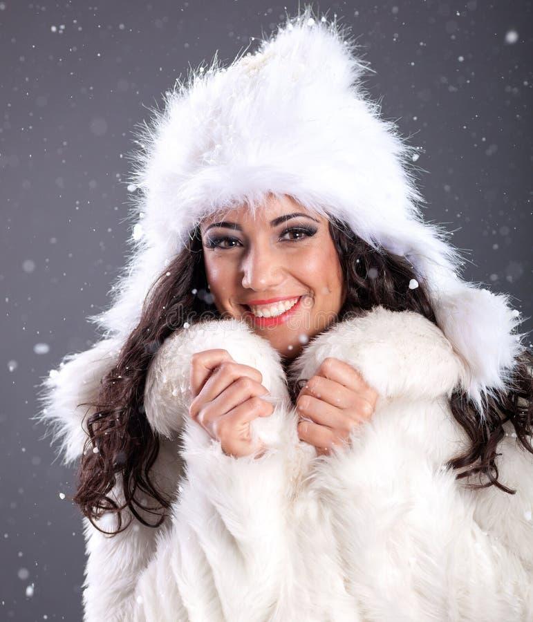 Stående av en härlig ung kvinna i ett vitt pälslag över sno arkivbild