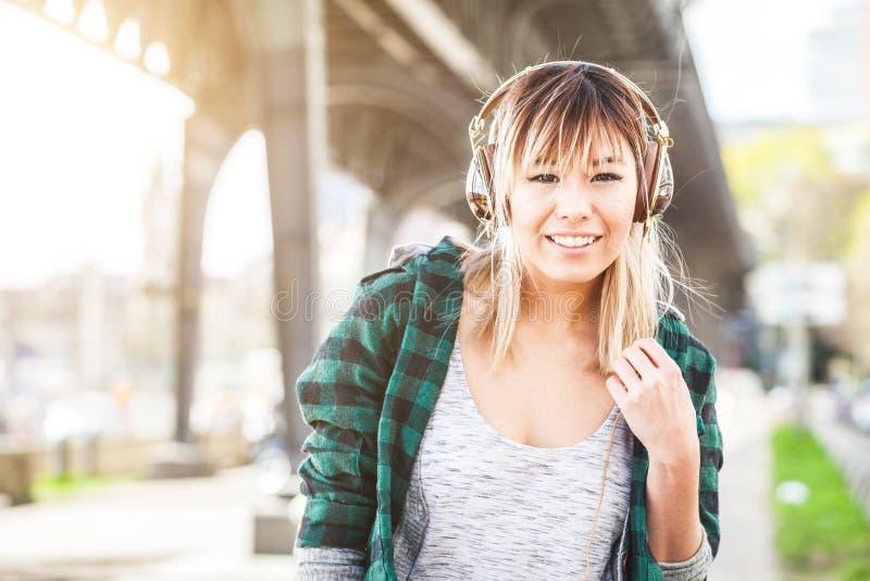 Stående av en härlig ung kvinna i Hamburg lyssnande musik arkivfoto