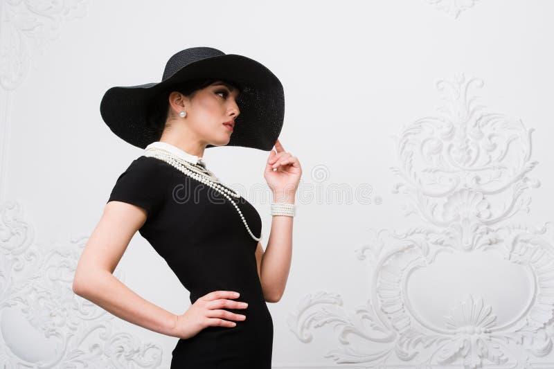 Stående av en härlig ung kvinna i retro stil i en elegant svart hatt och klänning över lyxig rokokoväggbakgrund royaltyfri fotografi