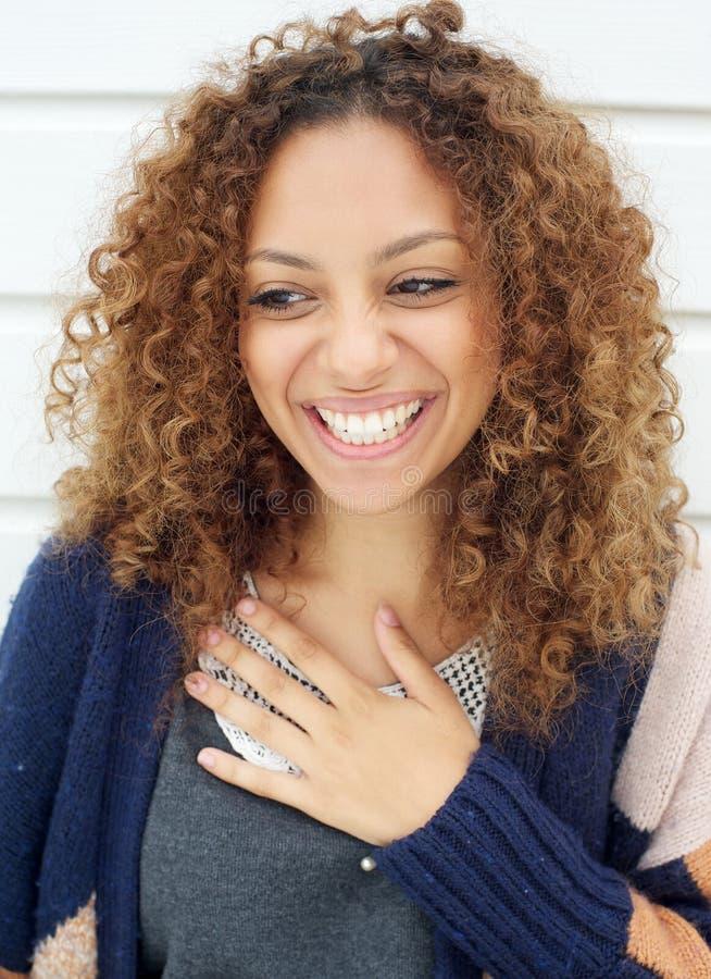 Stående av en härlig ung kvinna med att skratta för lockigt hår royaltyfri fotografi