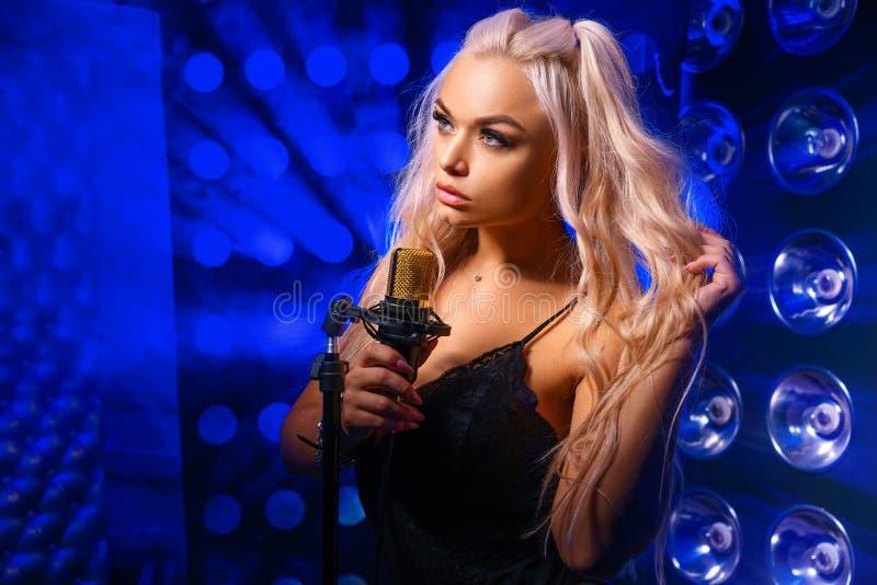 Stående av en härlig ung kvinna med ett mikrofonmode royaltyfri foto