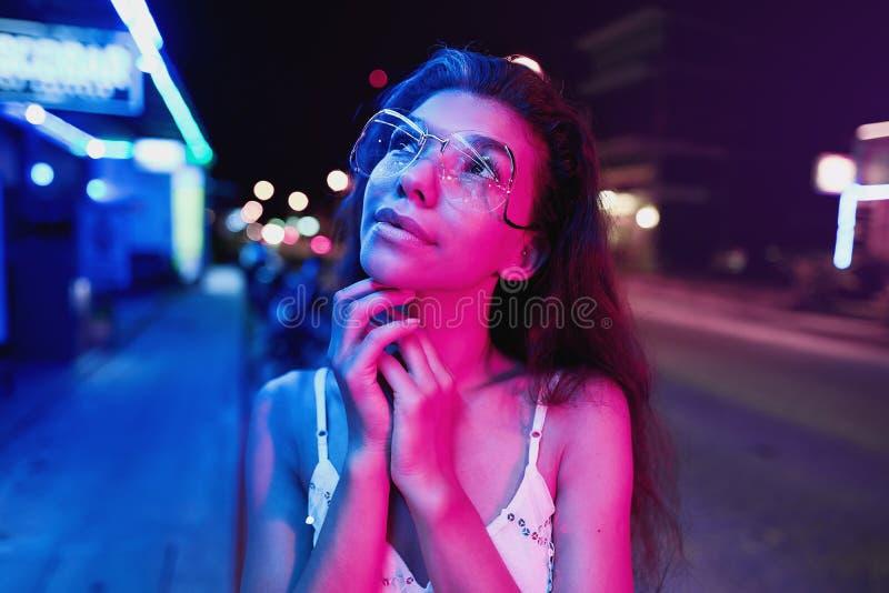 Stående av en härlig ung kvinna med exponeringsglas i futuristiskt neonljus arkivfoto