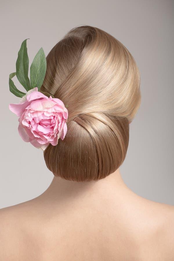 Stående av en härlig ung kvinna med en idérik frisyr, en grupp av hår arkivfoton