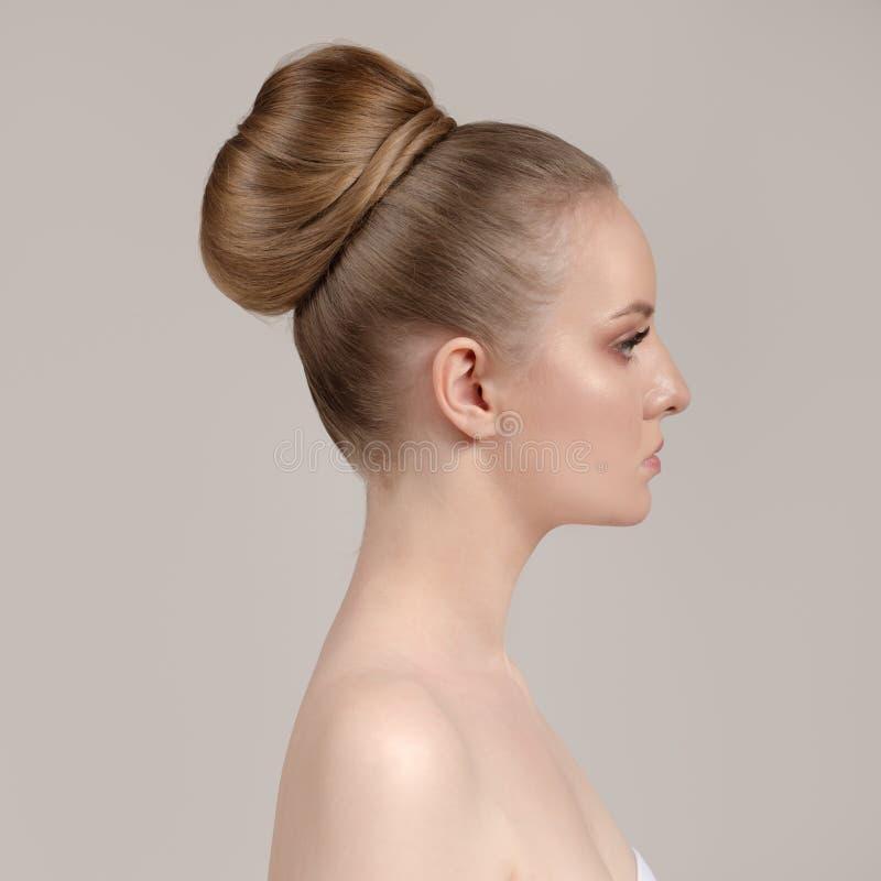 Stående av en härlig ung kvinna med en idérik frisyr, en grupp av hår royaltyfri fotografi