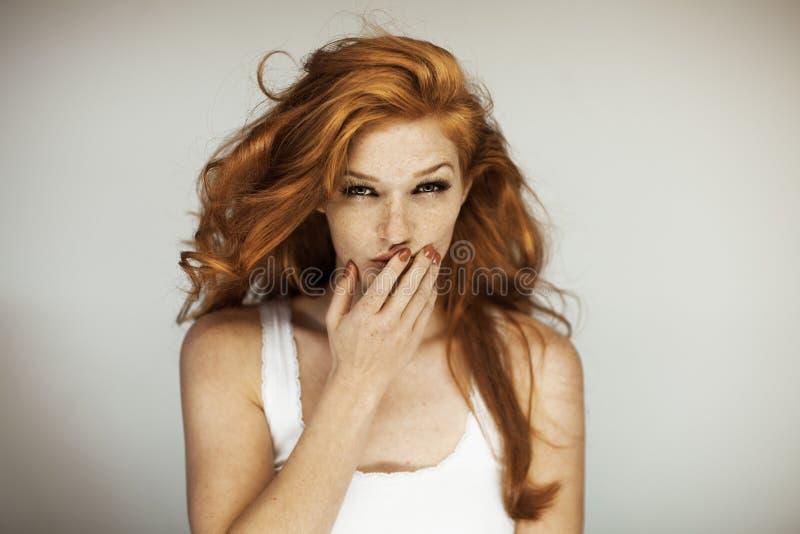 Stående av en härlig ung kvinna med långa röda lockigt hår och fräknar royaltyfri fotografi