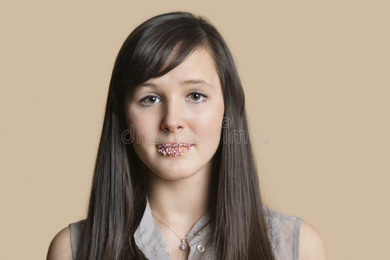Stående av en härlig ung kvinna med strilade kanter över kulör bakgrund royaltyfri fotografi