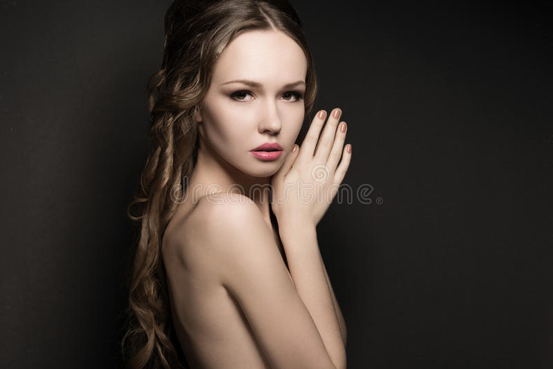 Stående av en härlig ung kvinna på mörk bakgrund arkivbild