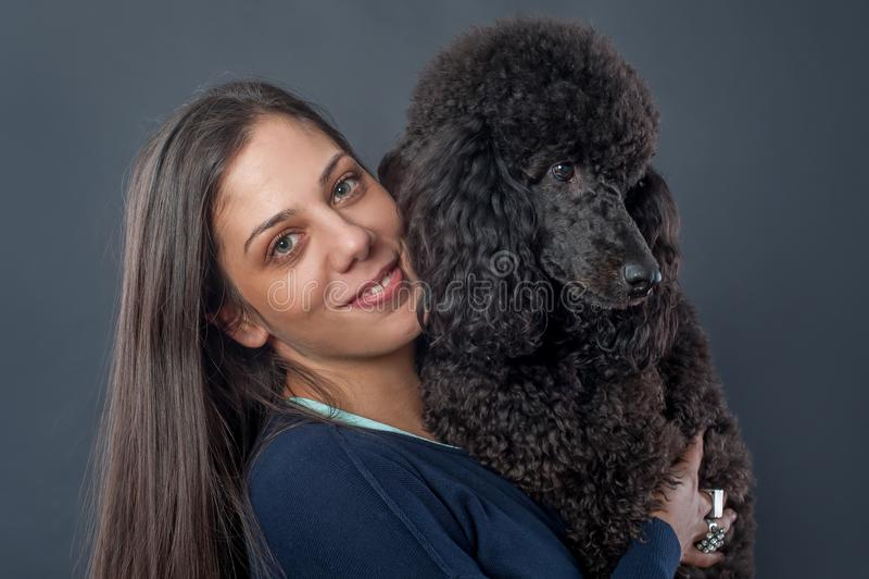 Stående av en härlig ung kvinna som kramar hennes härliga hund fotografering för bildbyråer