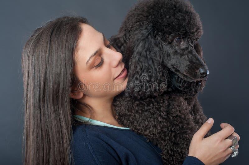 Stående av en härlig ung kvinna som kramar hennes härliga hund arkivbilder