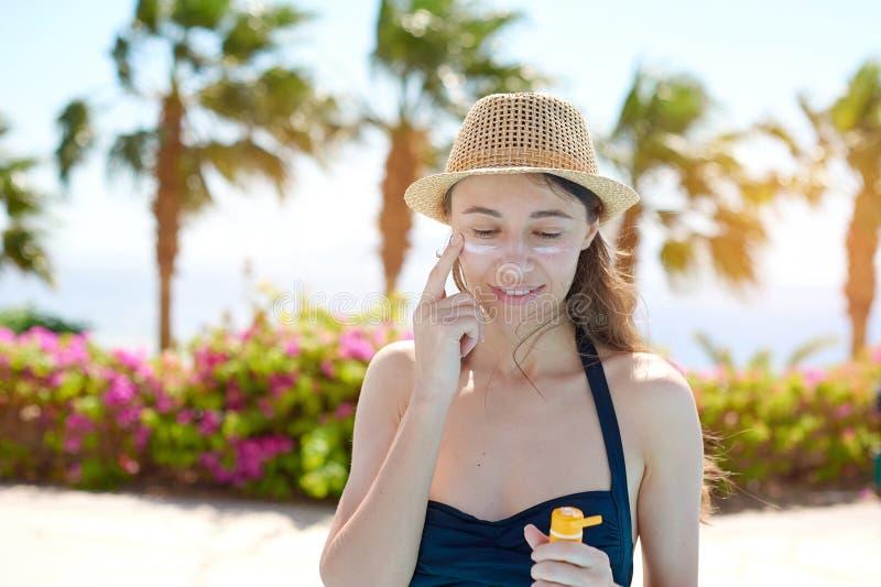 Stående av en härlig ung kvinna som ler i en baddräkt suddig framsida med solskyddskräm i hatt på havet arkivfoto