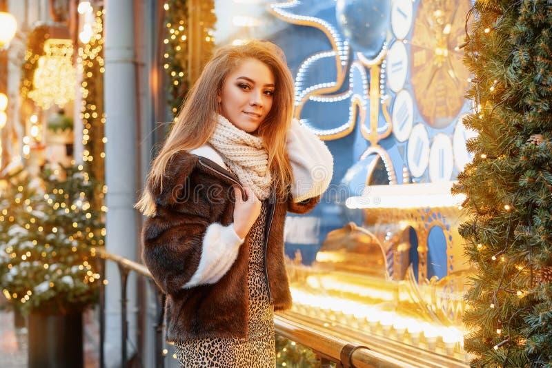 Stående av en härlig ung kvinna, som poserar på gatan nära det elegantly dekorerade julfönstret, festligt lynne royaltyfria foton