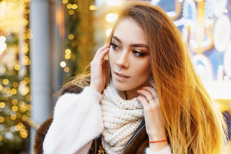 Stående av en härlig ung kvinna, som poserar på gatan nära det elegantly dekorerade julfönstret, festligt lynne fotografering för bildbyråer