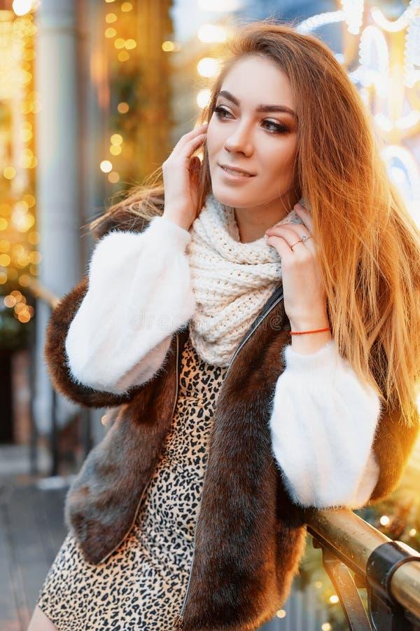 Stående av en härlig ung kvinna, som poserar på gatan nära det elegantly dekorerade julfönstret, festligt lynne royaltyfria bilder