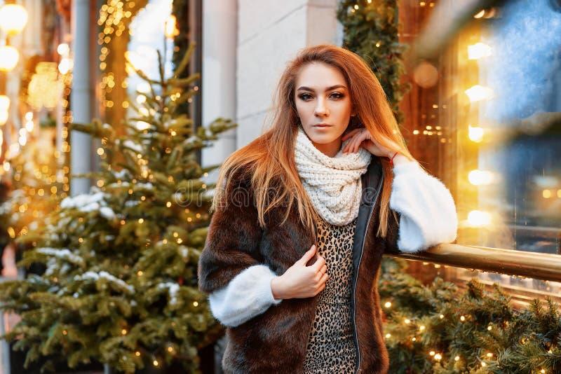 Stående av en härlig ung kvinna, som poserar på gatan nära det elegantly dekorerade julfönstret, festligt lynne arkivfoto