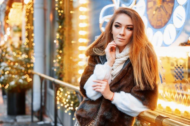 Stående av en härlig ung kvinna, som poserar på gatan nära det elegantly dekorerade julfönstret, festligt lynne royaltyfri bild