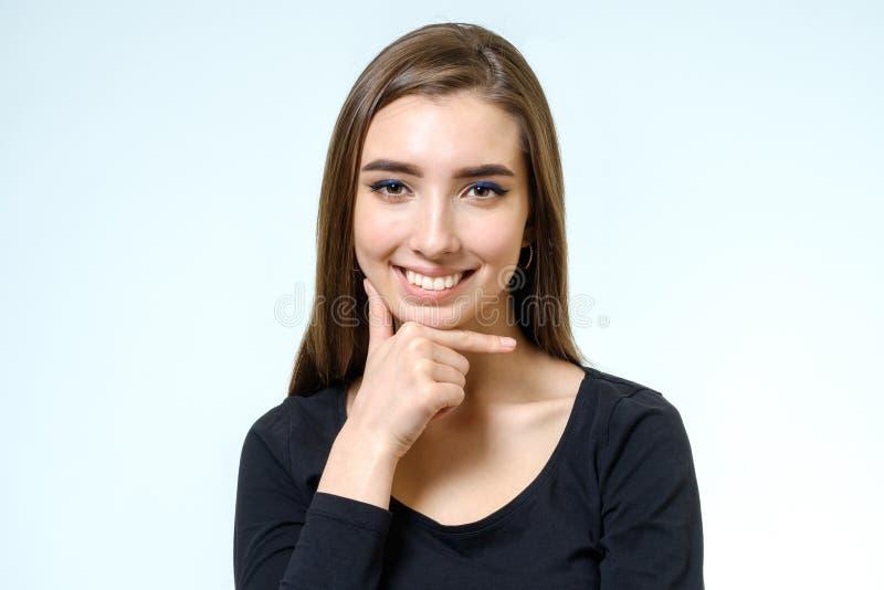 Stående av en härlig ung kvinna som ser kameran och smen royaltyfria foton