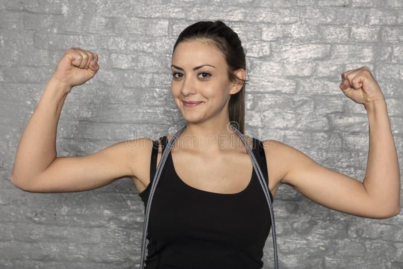Stående av en härlig ung kvinna som visar henne muskler royaltyfri bild