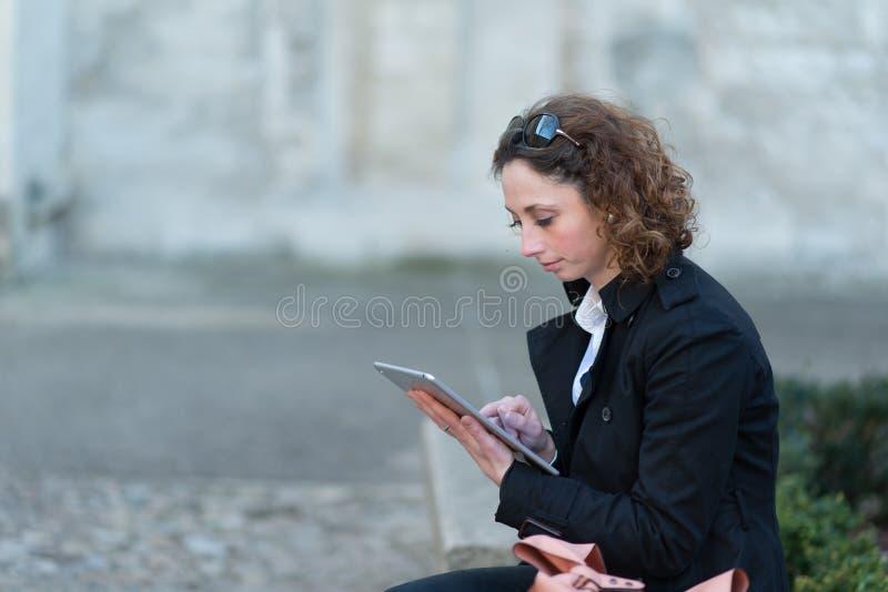 Stående av en härlig ung kvinna utanför med minnestavlan arkivfoto