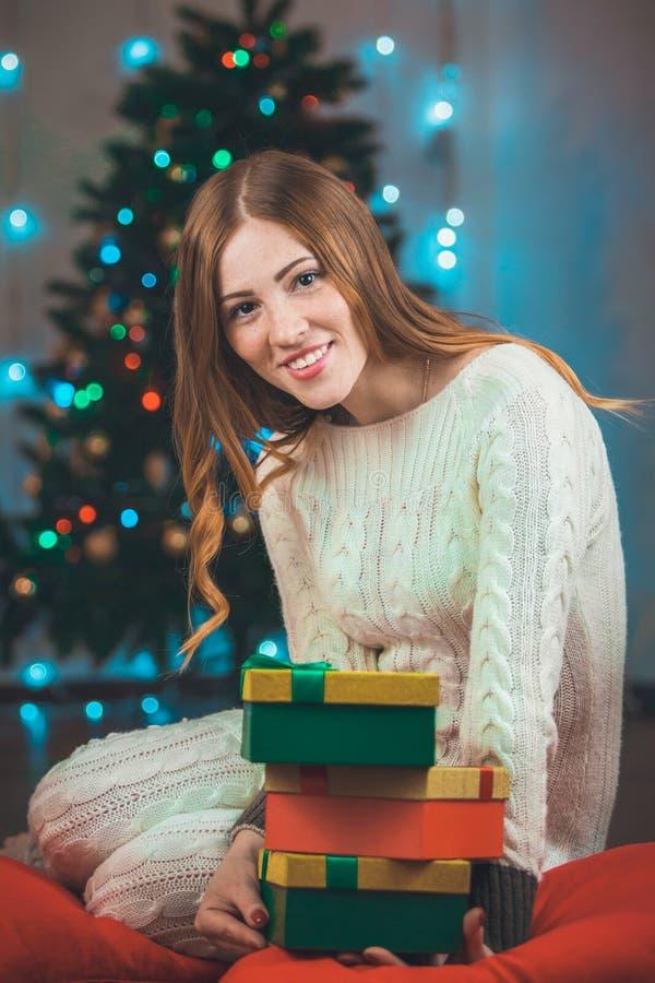 Stående av en härlig ung le kvinna på en bakgrund för julträd med gåvor i händer arkivbild